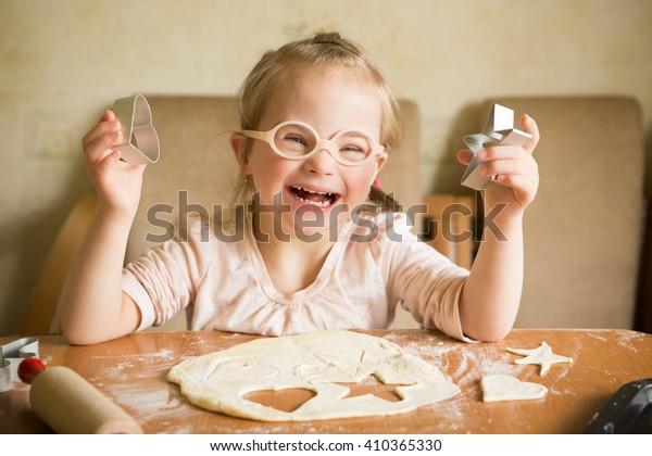 gelukkig meisje met het syndroom van Down bakt koekjes