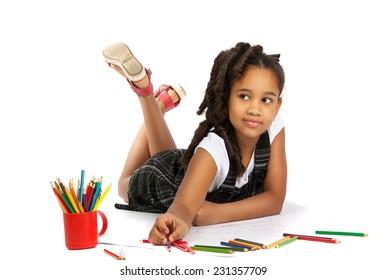 happy girl draws and writes lying on the floor