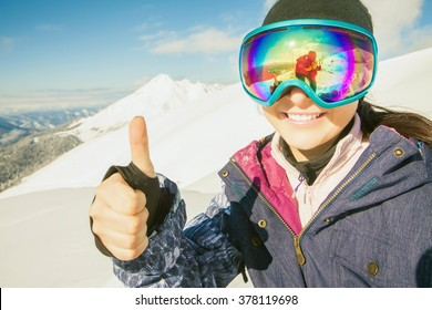 Happy girl dressed in ski or snowboard fashion mask goggles. Successful gesture thumbs up. Mountain landscape. Extreme adventure. Winter ski resort
