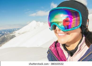 Happy girl dressed in ski or snowboard fashion mask goggles. Mountain landscape. Extreme adventure. Winter ski resort
