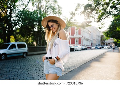 Happy girl dressed in white t-shirt and denim shorts is laughing on the street. Summer walks in sunlight with great emotions. Wonderful girl has fun and shows fun emotions.