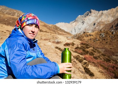 happy girl drinking water among the snow, high mountains of Himalayas