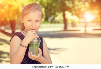 Happy girl drinks ice cold drink on a hot day in the park. Summer chilled drinks. Copy space.