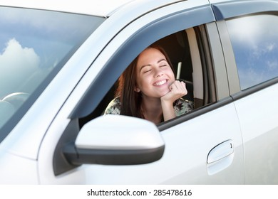 happy girl driver looks out  window of car