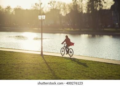 happy girl drives on bike near pond. image with tilt-shift effect
