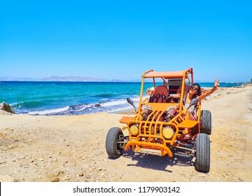 Ein glückliches Mädchen, das einen Buggy auf einer Düne am Strand mit dem Ägäischen Meer im Hintergrund fährt. Griechische Insel Kos. Region südliche Ägäis, Griechenland.