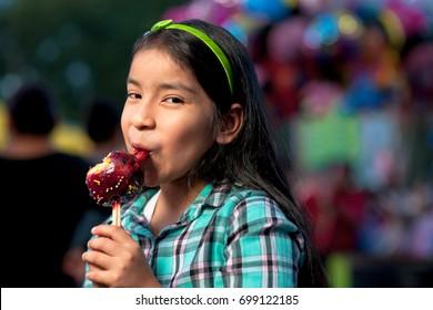 Happy girl eating a caramel apple at fair.