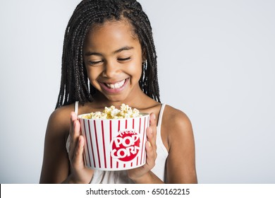 A happy girl eating popcorn over gray background