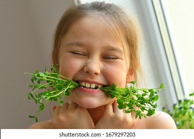 Happy girl eats pea microgreen .vegeterian concept.good appetite. spring avitaminosis.sprout vegetables germinated from high quality organic plant seed on linen mat.superfood.selective focus.