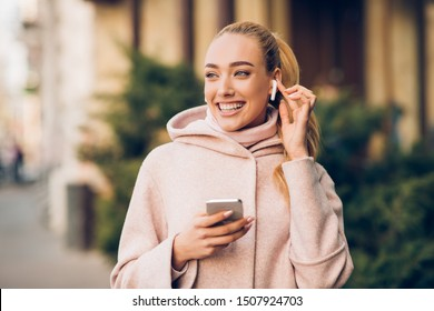 Happy girl enjoying music in airpods, walking in city center at autumn day