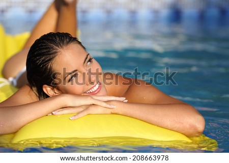 Happy girl enjoying summer vacations on a mattress in a pool and looking at side while thinking