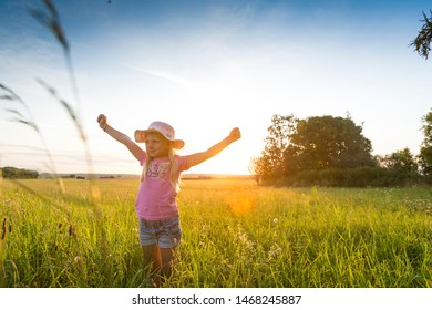 Happy girl enjoying the sunset at the countryside