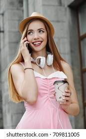 Happy girl enjoys her life, walks around the city in headphones and with a smartphone. Beauty, fashion.