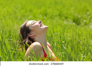 Happy girl face breathing fresh air and enjoying the sun in a meadow in a summer sunny day