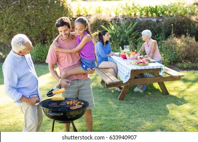 Happy girl, father and grandfather preparing barbecue in the park