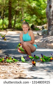 Happy girl feeding lorikeets at wildlife. Australia