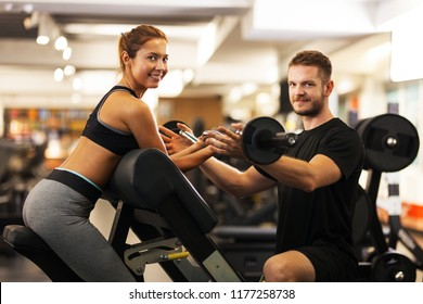 41d73fbdc48 happy girl with fitness coach lifting weights
