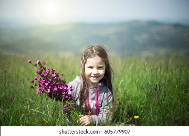 Happy girl with flowers in the meadow