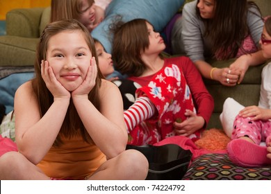 Happy girl with friends seated on floor at a sleepover