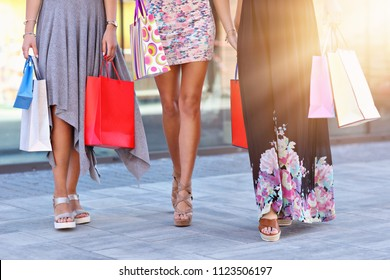 Happy girl friends shopping in mall