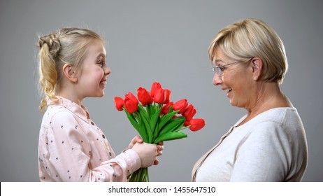 Happy girl giving flowers to grandmother, family tradition, holiday celebration