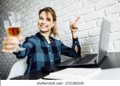 Fröhliches Mädchen mit Glas Wein sitzend am Tisch mit Laptop auf dem Hintergrund der weißen Ziegelwand.
