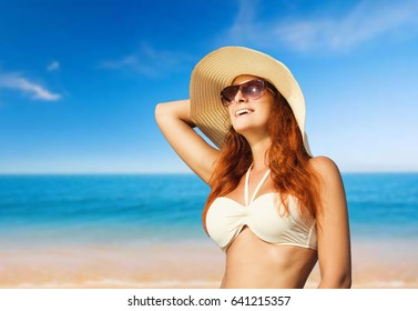 Happy girl in glasses and hat sunbathing on the sky background