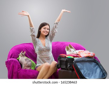 Happy girl going on vacation, studio shot on gray background