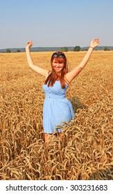 Happy girl in golden wheat