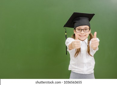 Happy girl in graduation cap near a school board showing thumbs up. Space for text