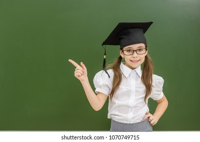 Happy girl in graduation cap standing near a school board and pointing away on empty space. Space for text