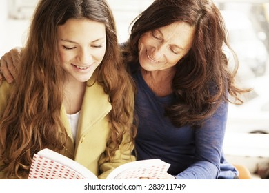 Happy girl and grandmother studying