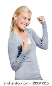 Happy girl in gray sweater with her fists up, isolated on white
