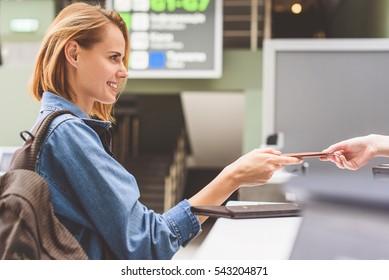 Happy girl handing over passport in airport