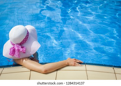 happy girl in a hat by the pool at sea