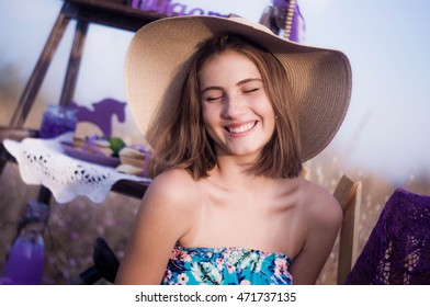 Happy girl in a hat in a field with decor