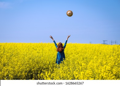 Happy girl in a hat walking in amazing field of yellow rapeseed in the countryside. Emotions
