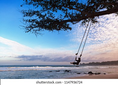Happy girl have fun swinging high in mid air. Flying up upside down on rope swing on sea beach. Travel adventure on paradise tropical island. Family lifestyle, activity on summer vacation with kids.
