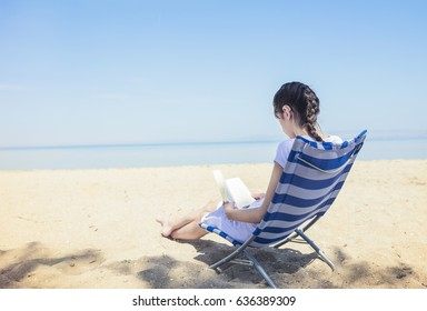 Happy girl with hearing aid siting on beach lounger and reading a book