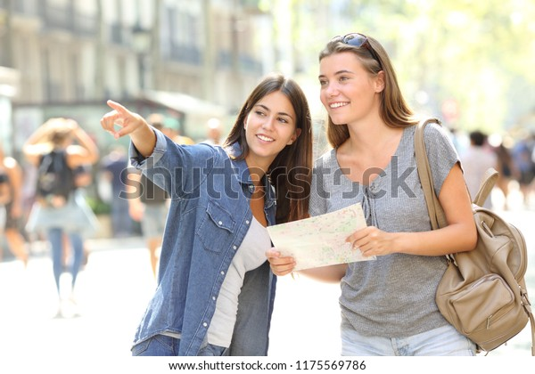 Happy girl helping to a tourist who asks direction in the street