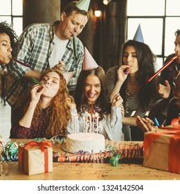 Happy girl with her birthday cake and friends around having fun. Friends birthday party concept