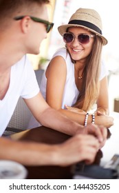 Happy girl and her boyfriend in sunglasses chatting in cafe