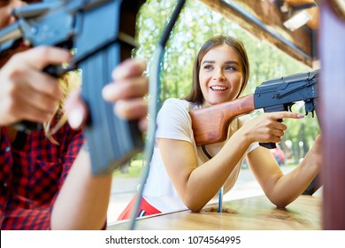 Happy girl and her friend with rifles shooting at range in contemporary theme park at leisure