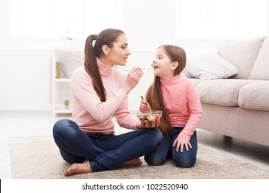 Happy girl and her mom eating a salad sitting on the floor at home. Mothers Day, relationship, motherhood, joint activities and interests, trust, support, caress, maternal warmth, caring concept