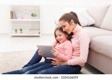 Happy girl and her mom using a tablet sitting on the floor at home. Mothers Day, relationship, motherhood, joint activities and interests, trust, support, caress, maternal warmth, caring concept