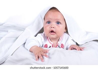 Happy Girl hiding in bed under a white blanket or coverlet. Girl at bed. Child in bed. isolated on white background.