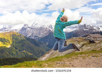 happy girl hikers jumping at the mountains Dolomites, Italy.