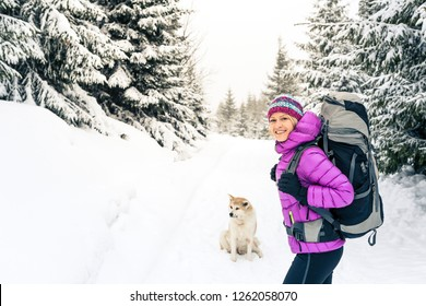 Happy girl hiking in white winter forest with akita dog. Recreation fitness and healthy lifestyle outdoors in nature. Inspirational winter landscape.