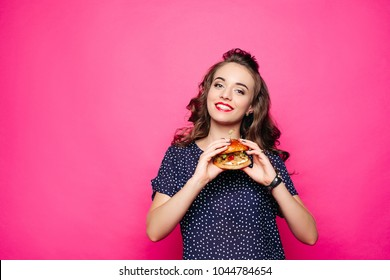 Happy girl holding a hamburger. Happy offers to try a sandwich, looking apetitnym with a look at you. The student is eating a hamburger. Isolated on a pink background