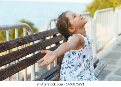 happy girl holding hands up sitting on bench